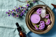 Essential Oil And Its Uses Concept With Copy Space. Aromatic Candle And A Vial For Perfume Lavender And Vervain, Shot From Above On A Blue Background