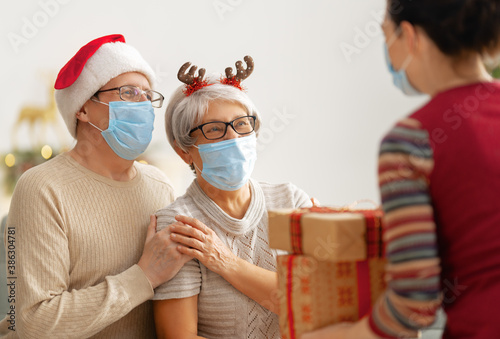 Obraz People with gifts wearing facemasks on Christmas. - fototapety do salonu