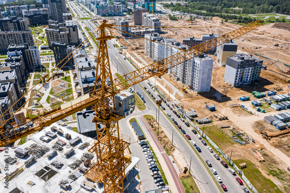 Fototapeta development of new residential area. building site with high-rise building and cranes. aerial view