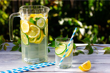 A Decanter Of Cool Water With Slices Of Lemon And Lime On A Light Wooden Table.