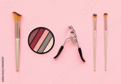 Photographie Set of makeup brushes with eyelash curler and eyeshadows on color background