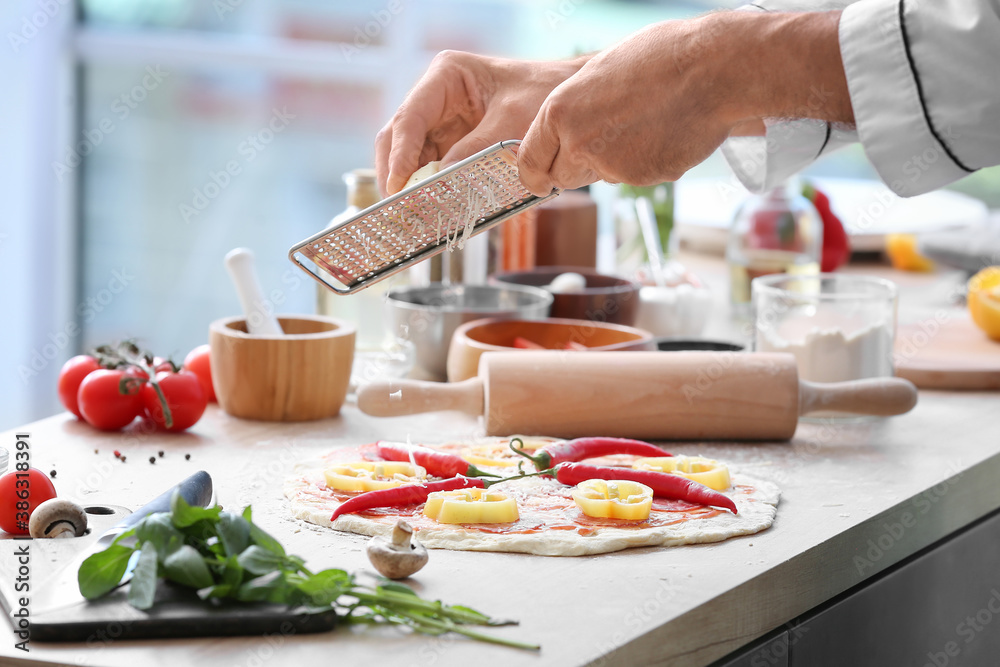 Fototapeta Mature male chef cooking tasty pizza in kitchen, closeup