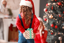 Cute Girl Hiding Gift For Her Parents On Christmas Eve