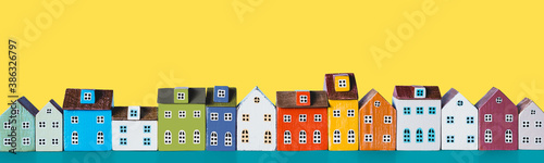 Obraz Row of wooden miniature colorful retro houses on a yellow background - fototapety do salonu