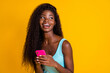 canvas print picture - Photo portrait of young curly african american woman holding phone in two hands laughing wearing blue singlet isolated on bright yellow colored background