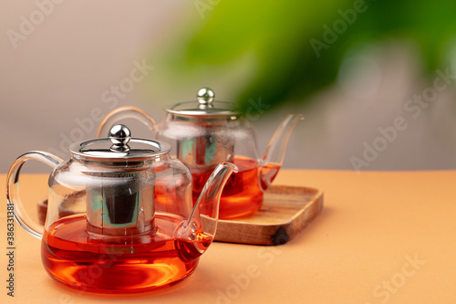 Fotografía Glass teapot with black tea on background of blurred foliage