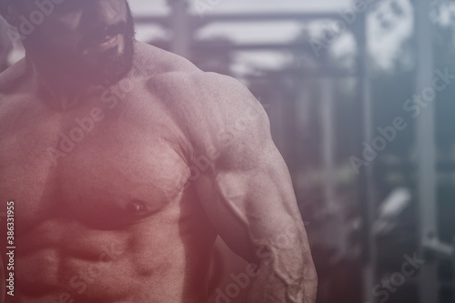 strong young bearded handsome athlete man with muscular physique body on street outdoors workout sport ground with fitness equipment with copy space