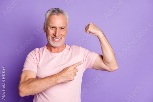 Valokuva Photo of pensioner old man raise arm direct finger demonstrate biceps wear pink