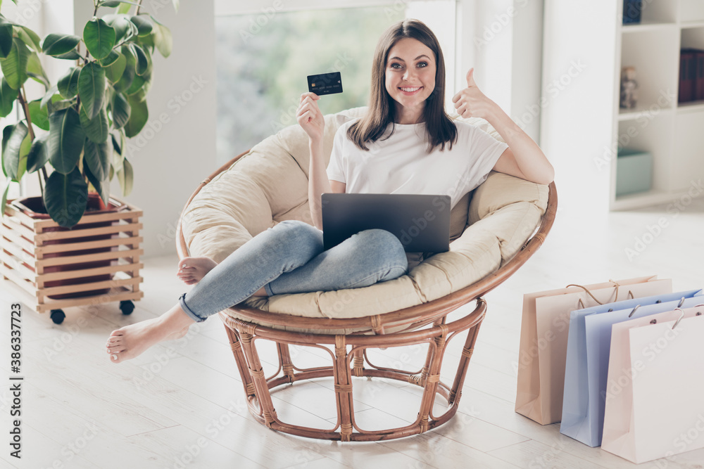 Fototapeta Full body photo of positive girl show order purchase through laptop show thumb-up sign sit wicker chair in house indoors
