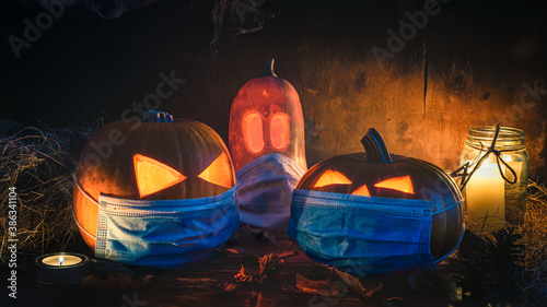 Halloween themed background, spooky pumpkins wearing face masks and candles in a dark setting