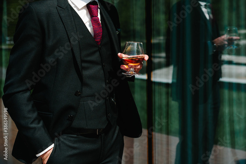 Obraz Close up of man hold glass of whiskey, drink alcoholic beverage in the pub. Business man drinking brandy. - fototapety do salonu