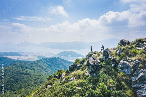 Obraz People taking photos on Footpath on a sharp mountain in Clear Water Bay, Sai Kung, Hong Kong. Hiking destination, clear weather in Autumn - fototapety do salonu