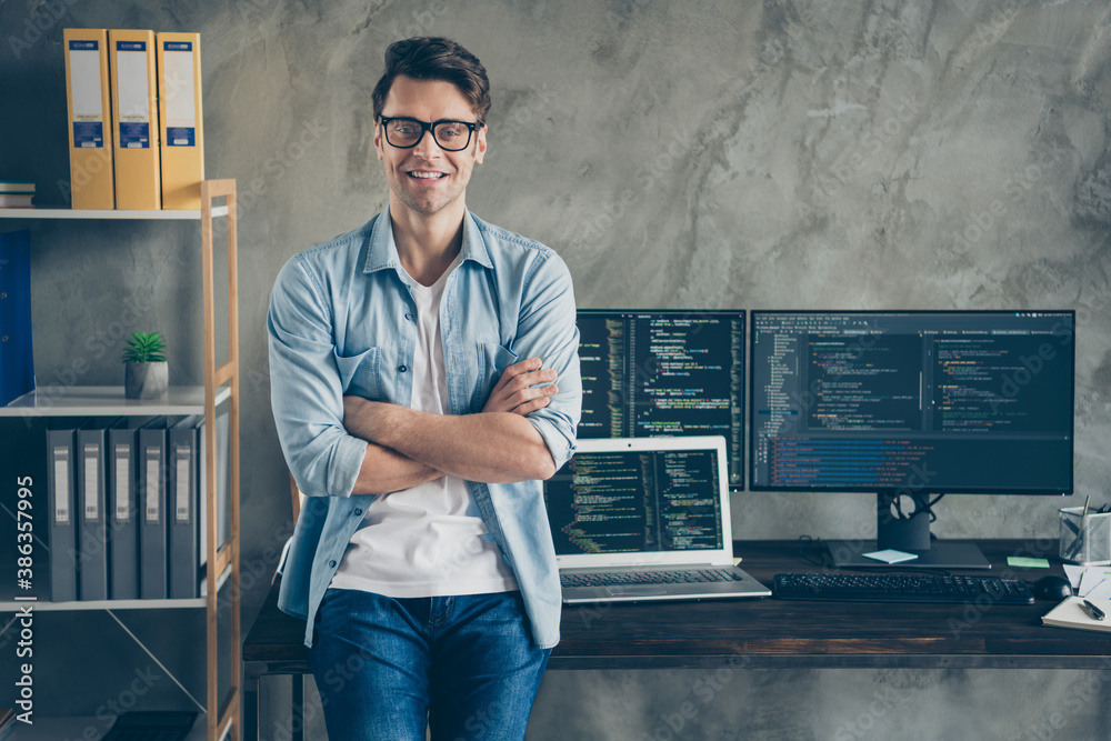 Fototapeta Portrait of his he nice attractive content cheerful cheery geek guy technician security manager folded arms at modern industrial interior style concrete wall work place station