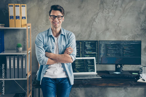 Portrait of his he nice attractive content cheerful cheery geek guy technician security manager folded arms at modern industrial interior style concrete wall work place station
