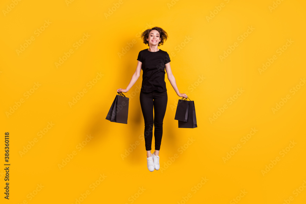 Fototapeta Full length body size view of attractive cheerful funky girl jumping carrying packages bargain store isolated bright yellow color background