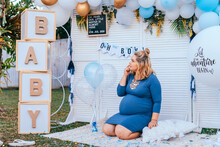 Baby Shower - Pregnant Woman With A Big Tummy Sits On The Floor On A Party Setup
