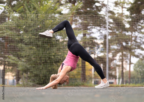Attractive fit blond woman practice down dog exercise with one leg up and bend, in split Canvas