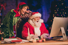 Photo Portrait Of Shocked Santa Claus And Elf Browsing Internet On Pc