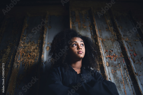 Fototapeta Portrait of mixed-race teenager girl standing indoors in abandoned building. obraz
