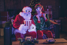 Photo Portrait Of Shocked Santa Claus And Elf Holding Popcorn Watching Movie On Sofa In 3d Glasses