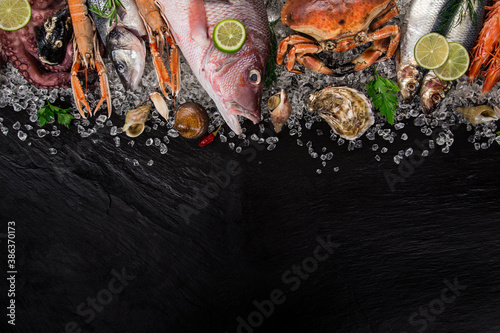 Fototapeta Fresh tasty seafood served on black stone table. Top view. Close-up. obraz
