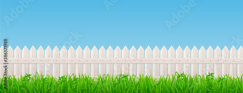 Fotomural White wooden picket fence and green grass on background of blue sky