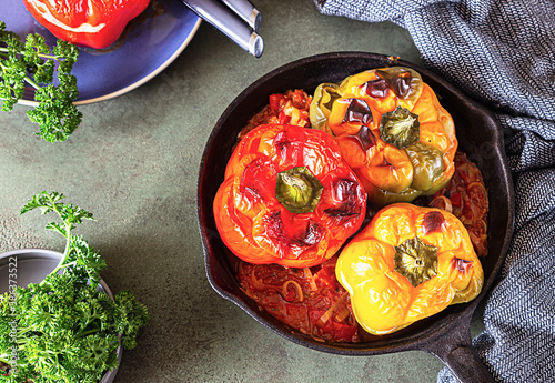 Tela Baked sweet bell peppers stuffed with chicken or turkey, corn and herbs in cast iron pan, green stone background