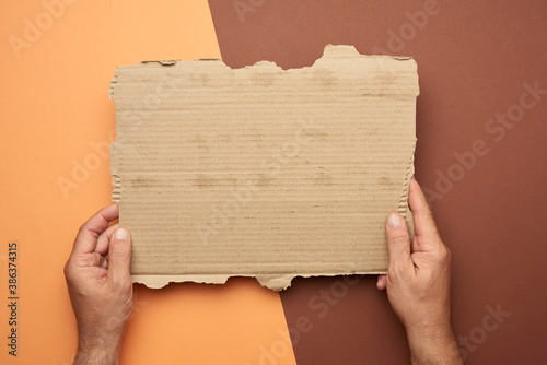Valokuva two male hands hold a blank torn piece of brown paper