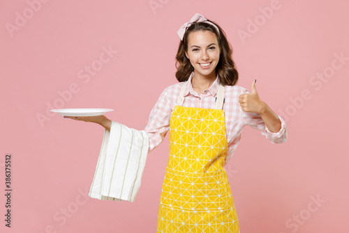 Cheerful smiling young woman housewife 20s in yellow apron hold empty plate dishcloth towel showing thumb up doing housework isolated on pastel pink background studio portrait Fototapeta