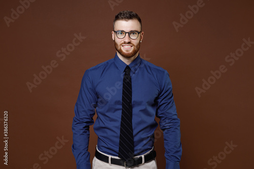 Obraz Smiling successful handsome bearded young business man in blue shirt tie eyeglasses looking camera isolated on brown colour background studio portrait. Achievement career wealth business concept. - fototapety do salonu