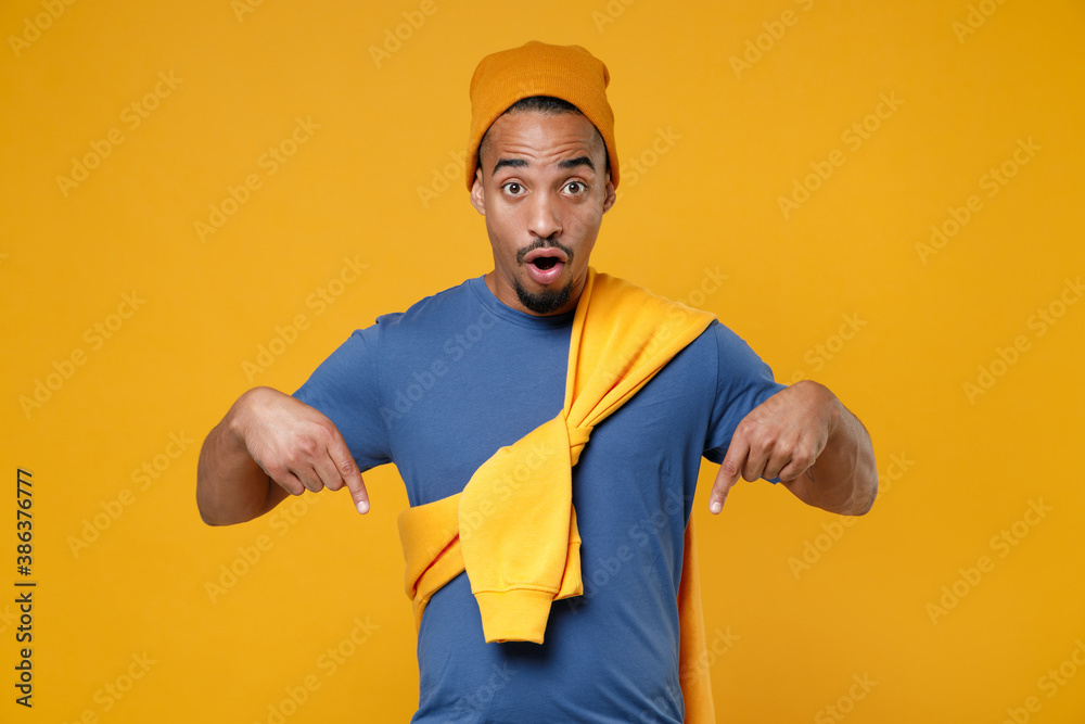 Fototapeta Shocked amazed young african american man 20s in basic casual blue t-shirt hat pointing index fingers down on mock up copy space looking camera isolated on bright yellow background, studio portrait.