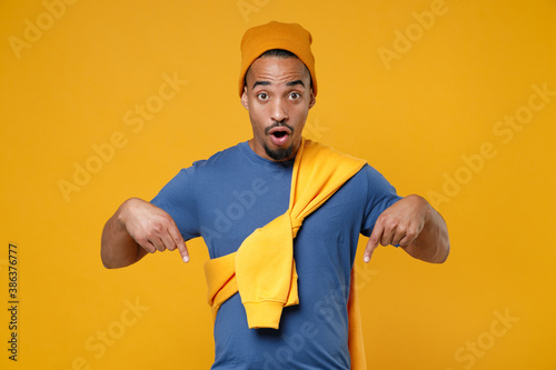 Shocked amazed young african american man 20s in basic casual blue t-shirt hat pointing index fingers down on mock up copy space looking camera isolated on bright yellow background, studio portrait Fototapeta