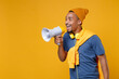 Excited cheerful funny young african american man 20s wearing basic casual blue t-shirt hat standing screaming in megaphone looking aside isolated on bright yellow colour background, studio portrait.