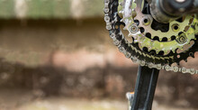 Close-up Of Gears And A Chain To Drive A Bicycle. The Chain Is Dirty And Greasy. Copy Space