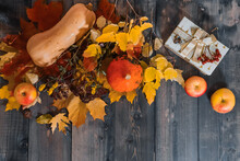 On A Gray Wooden Tabletop On Yellow Autumn Leaves, Autumn Yellow Apples, Flowers, Orange And Yellow Pumpkins, An Elegant Box Decorated With A Bunch Of Mountain Ash Are Laid Out..