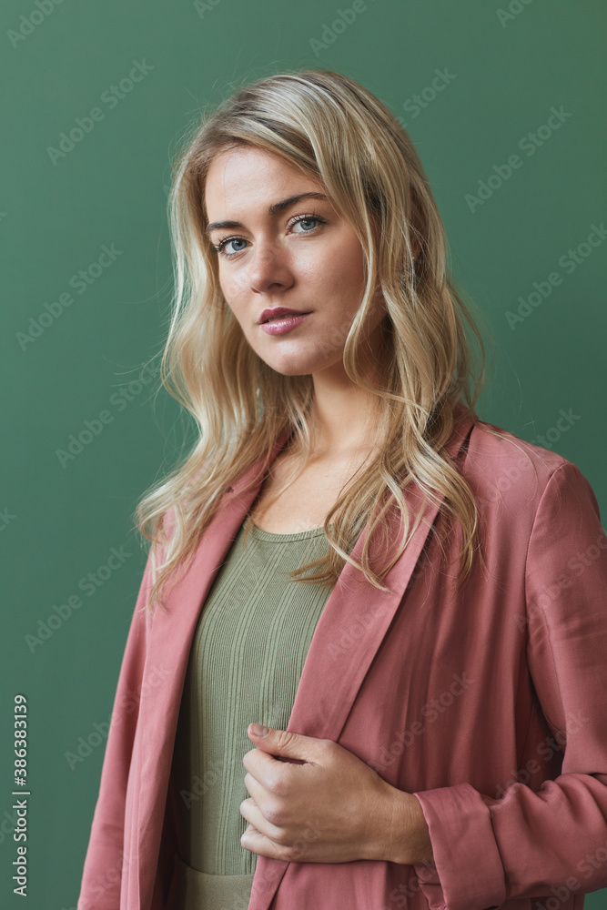 Fototapeta Vertical waist up portrait of elegant blonde woman wearing dusty pink jacket and looking at camera while posing against green background in studio
