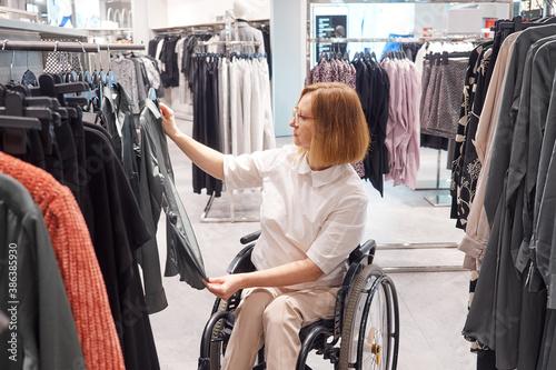 Slika na platnu Woman shopper in a wheelchair chooses clothes in the mall