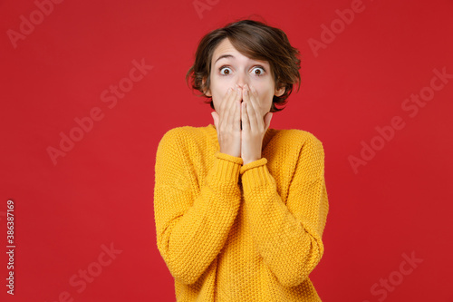 Shocked amazed surprised excited young brunette woman 20s wearing basic casual yellow sweater stand covering mouth with hands looking camera isolated on bright red colour background studio portrait.