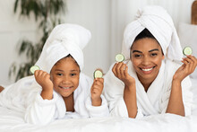 Beauty Time. African Mom And Daughter In Bathrobes Posing With Cucumber Slices