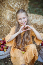 Nice Smiling Girl With Blue Eyes And Blonde Hair Shows A Heart With Her Hands In Front Of Rural Background Of Haystack And Apple Harvest.
