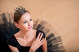 portrait of a young ballerina in black tutu and crown