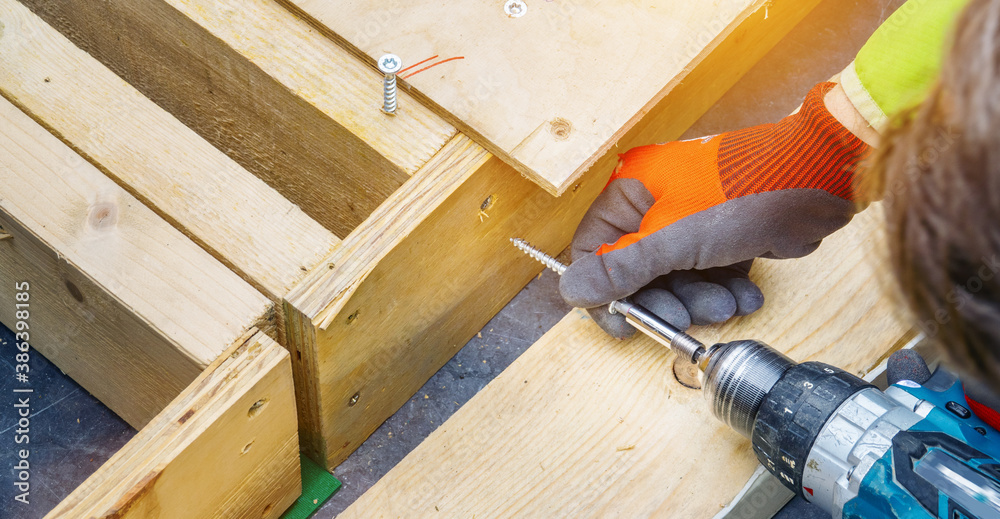 Fototapeta versatile craftsman working with wood to build a house on a summer day, DIY concept