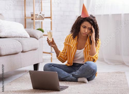 Fototapeta Sad black woman drinking wine during virtual party