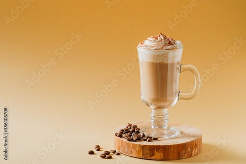 Coffee latte in glass with milk foam on wooden pedestal or stand on yellow Fototapet