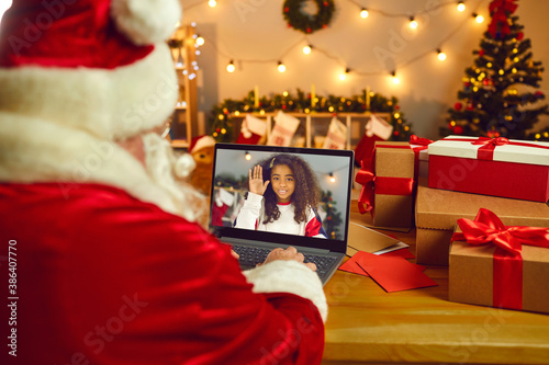 Santa Claus video calling a happy African American girl to wish her Merry Christmas - 386407770