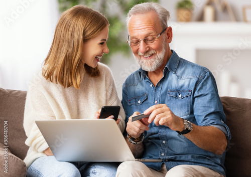 Young woman with father shopping online at home. - 386418704