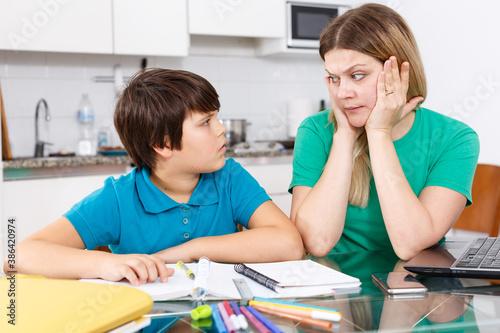 Obraz Portrait of emotional woman and boy doing homework with laptop at kitchen - fototapety do salonu