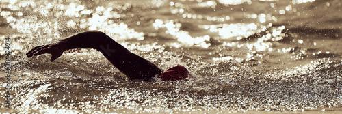 Fotografie, Obraz Silhouette man triathlon iron man athlete swimmers swimming