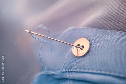 Fotografia, Obraz Needle with blue thread sewing button.