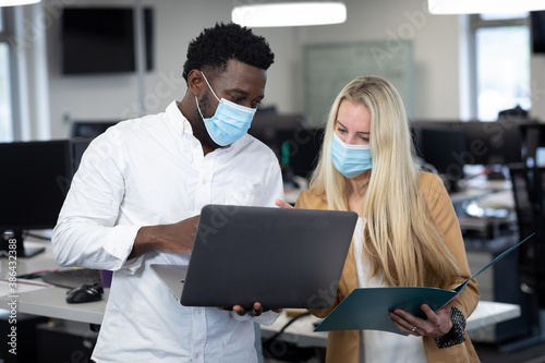 Businessman and businesswoman wearing face masks working together at modern office
